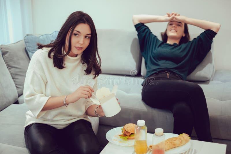 Flicka som äter pasta, medan hennes flickvän vilar royaltyfria bilder