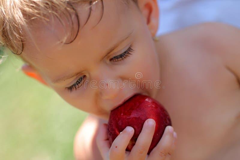 Flicka som äter persikan royaltyfri fotografi