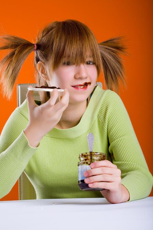 Flicka som äter rån arkivbild