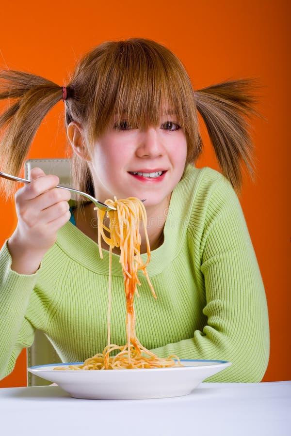 Flicka som äter spagetti royaltyfria bilder