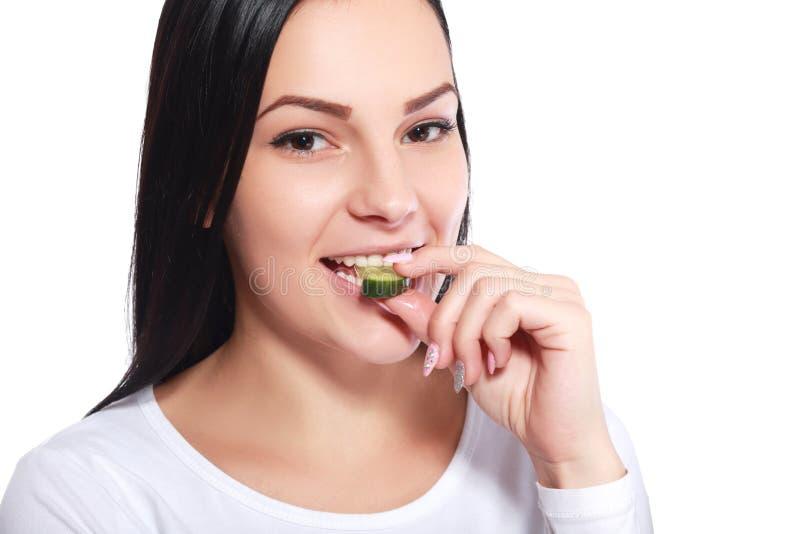 Flicka som äter stycket av gurkan royaltyfria foton