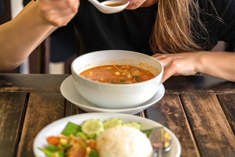 Flicka som äter Tom Yam Kung, thailändsk kokkonst close upp royaltyfria foton