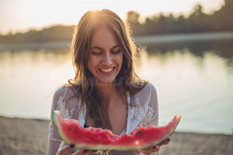 Flicka som äter vattenmelon och att le royaltyfri foto