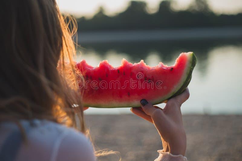 Flicka som äter vattenmelon och ser vattnet arkivfoto