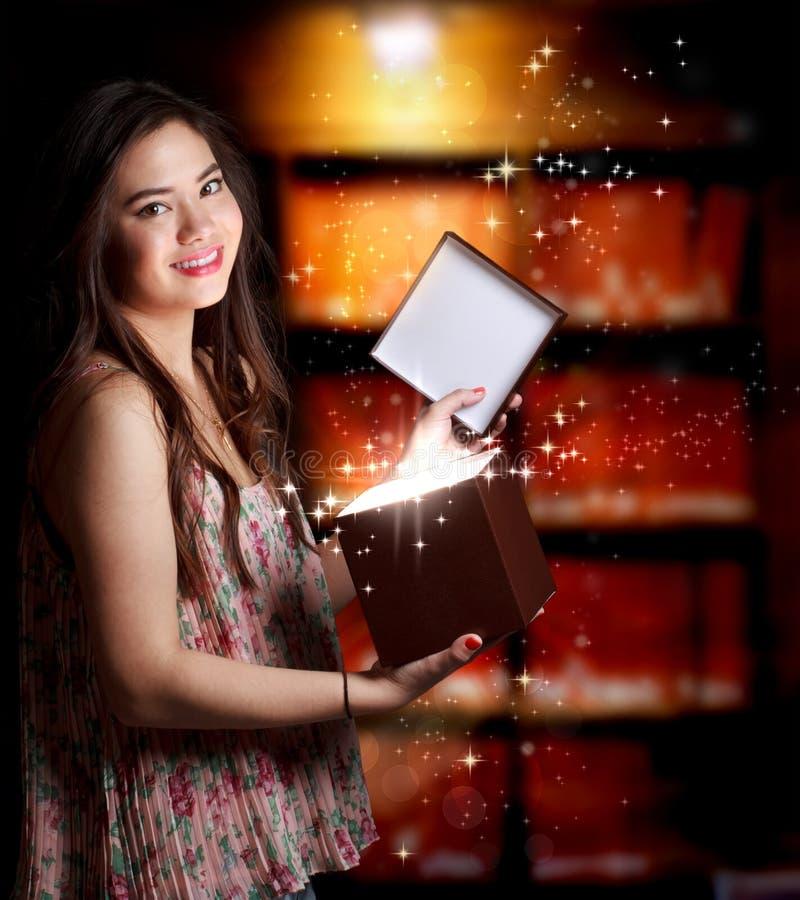Flicka som öppnar en gåvaask arkivbild