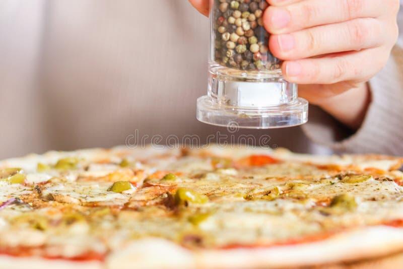 Flicka som överst tillfogar kryddor av pizza arkivfoto