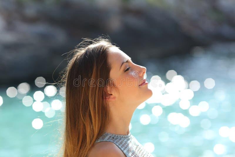 Flicka som andas ny luft på en tropisk strand på ferier arkivfoto