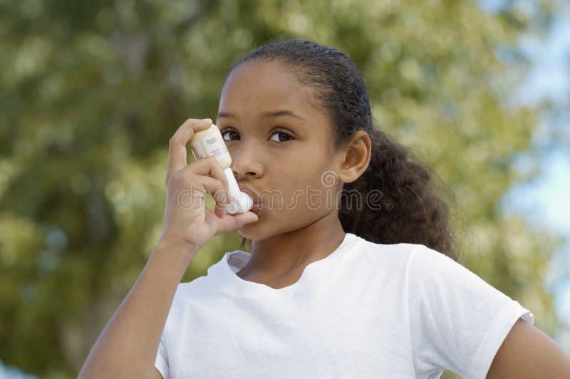 Flicka som använder astmainhalatorn royaltyfria bilder