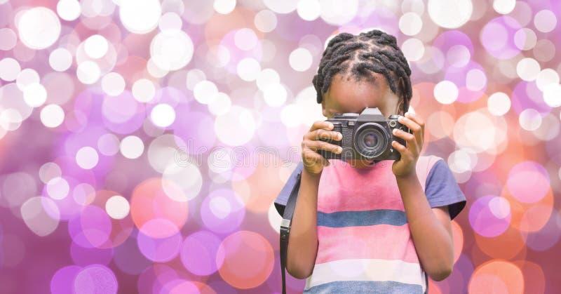 Flicka som använder den digitala kameran över bokeh royaltyfria foton
