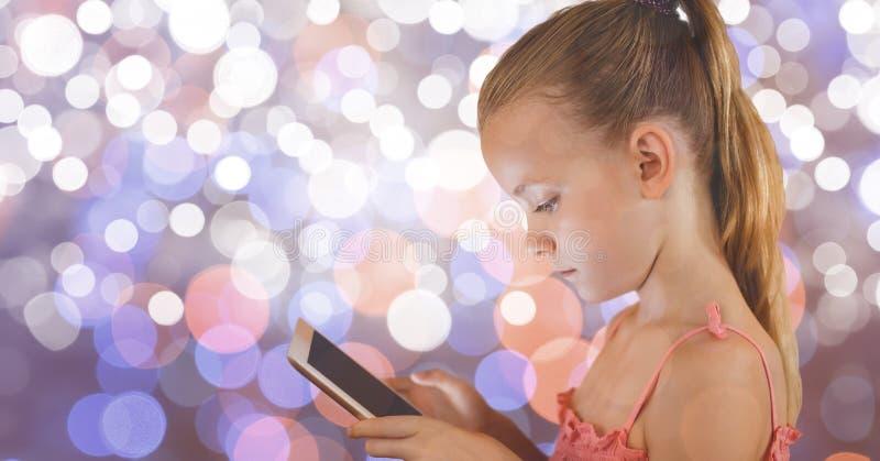 Flicka som använder den digitala minnestavlan över bokeh arkivbilder