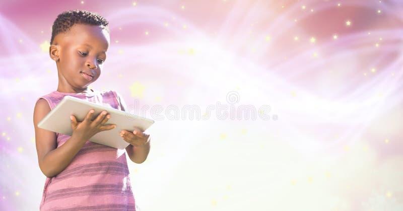 Flicka som använder den digitala minnestavlan över glödande bokeh för rosa färger royaltyfria foton