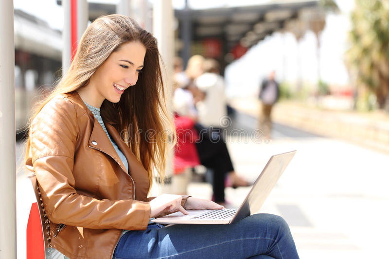 Flicka som använder en bärbar dator, medan vänta i en drevstation arkivbild