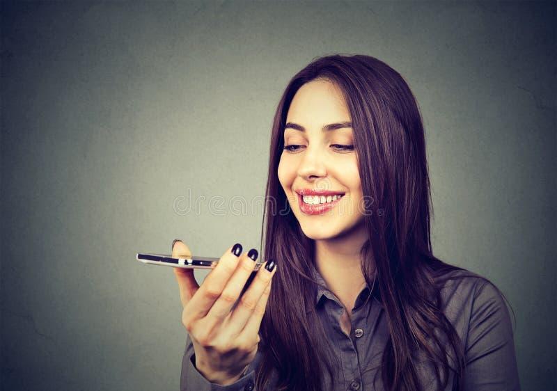 Flicka som använder en smart funktion för telefonstämmaerkännande på linje arkivbild