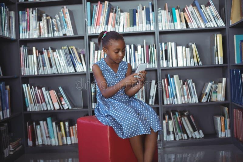 Flicka som använder mobiltelefonen, medan sitta mot bokhyllan i arkiv arkivbild