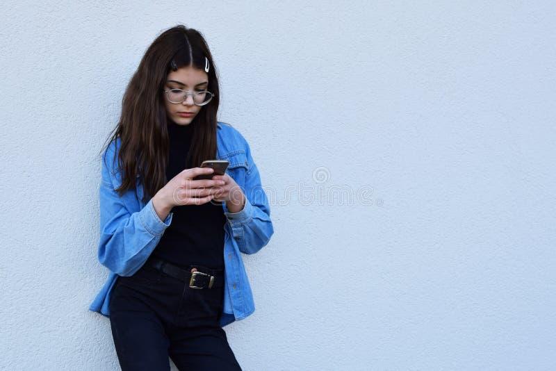 Flicka som använder smartphonen arkivbild