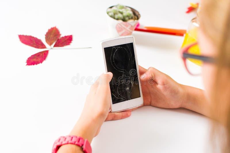 Flicka som använder telefonen med den brutna skärmen arkivfoton