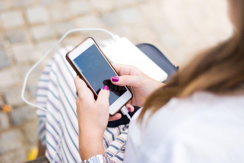 Flicka som använder telefonen, medan ladda på maktbanken royaltyfri foto