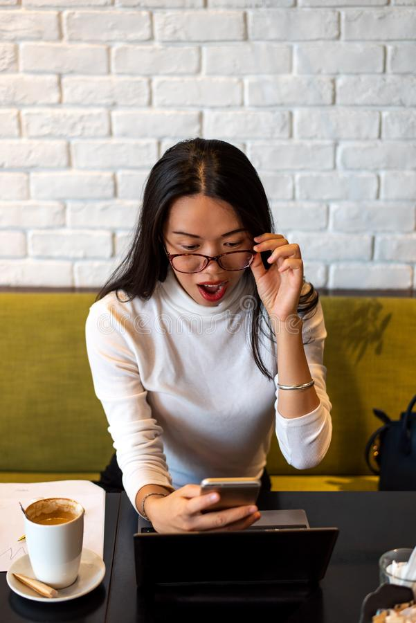 Flicka som använder telefonen och arbetar i en cafeteria royaltyfri fotografi