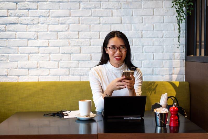 Flicka som använder telefonen och arbetar i en cafeteria royaltyfri foto