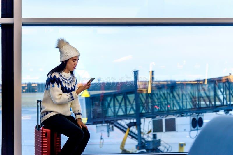 Flicka som använder telefonen och sitter på resväskan på flygplatsen arkivbild