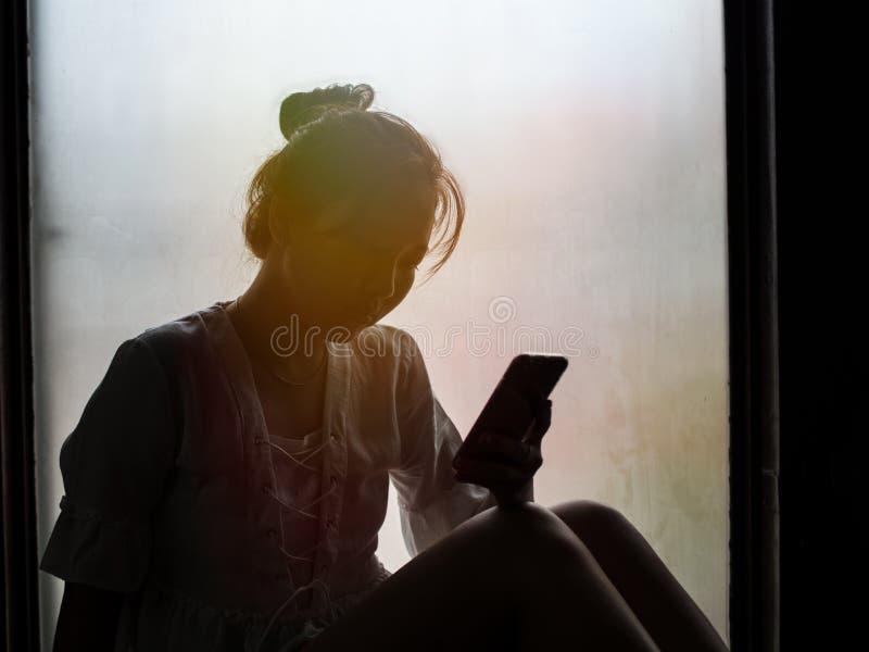 Flicka som använder telefonen som sitter på fönstret arkivbild