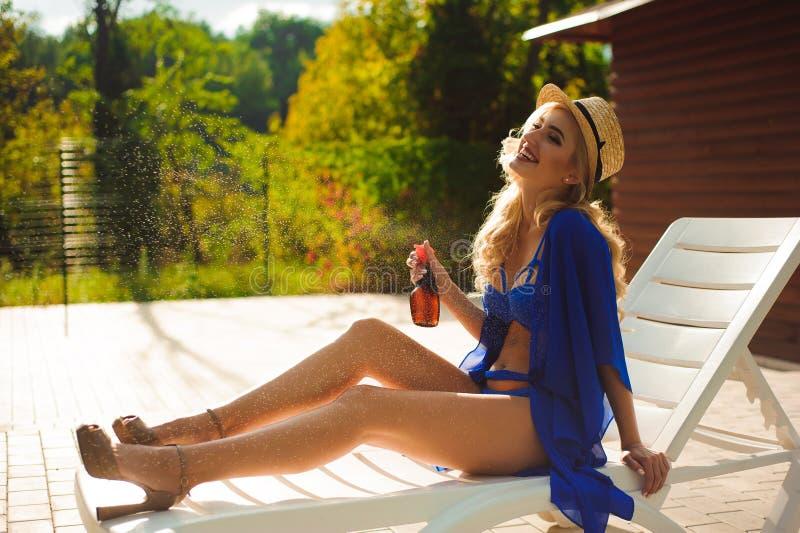 Flicka som applicerar sunscreen på hennes ben och ligger på en soldagdrivare royaltyfri fotografi