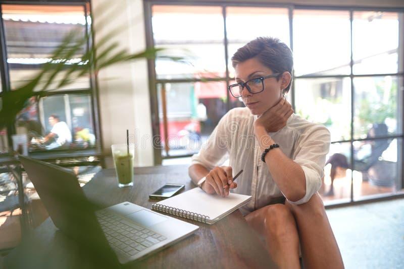 Flicka som arbetar i ett kafé Frilans- begrepp arkivfoto