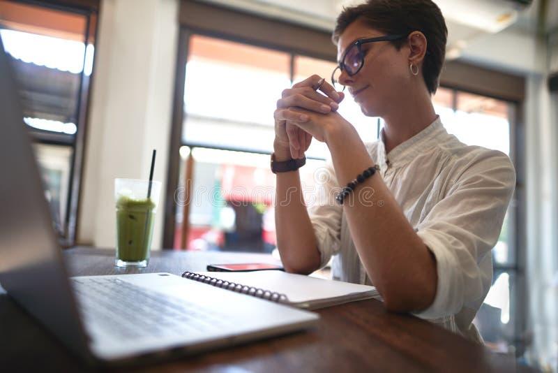 Flicka som arbetar i ett kafé Frilans- begrepp arkivbild