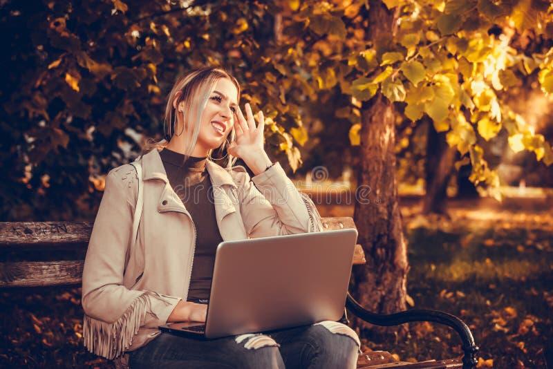 Flicka som arbetar på en bärbar dator i parkera arkivfoton