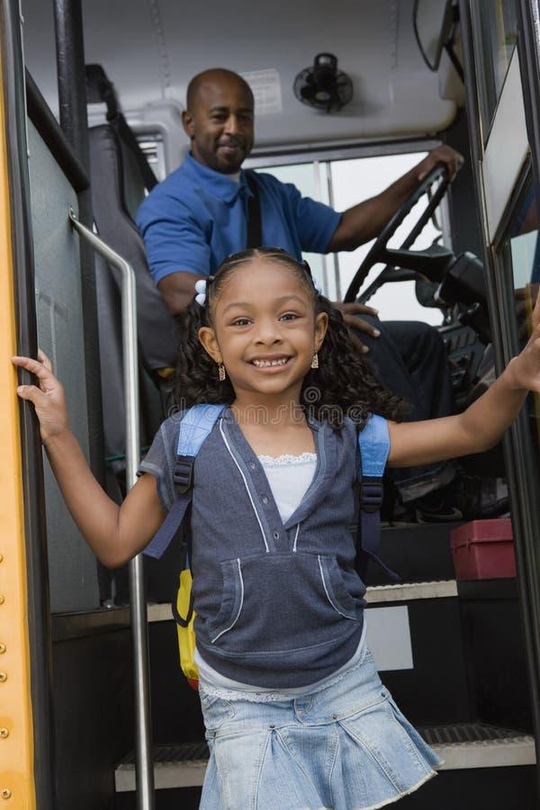 Flicka som av får skolbussen fotografering för bildbyråer