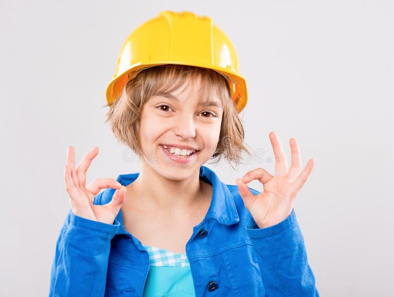 Flicka som bär den gula hårda hatten fotografering för bildbyråer