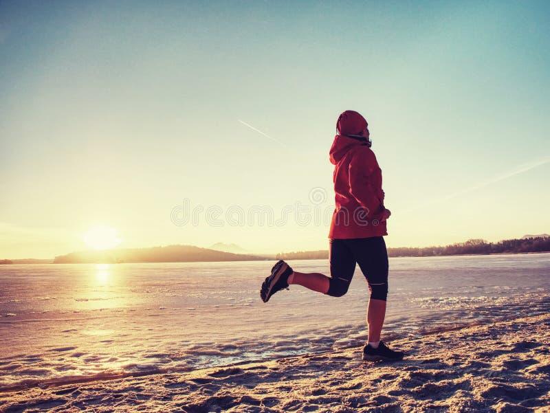 Flicka som bär den röda svarta sportswearen och spring på snö royaltyfria foton