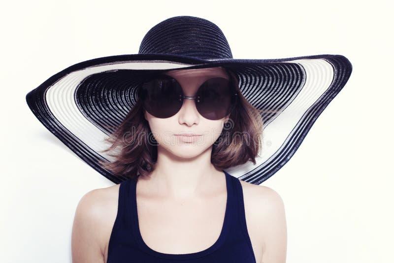 Flicka som bär en sommarhatt och solglasögon royaltyfri bild