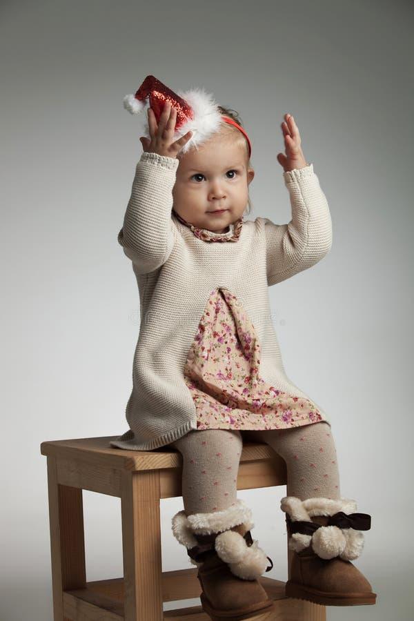 Flicka som bär santa hattsammanträde med händer i luften arkivfoton