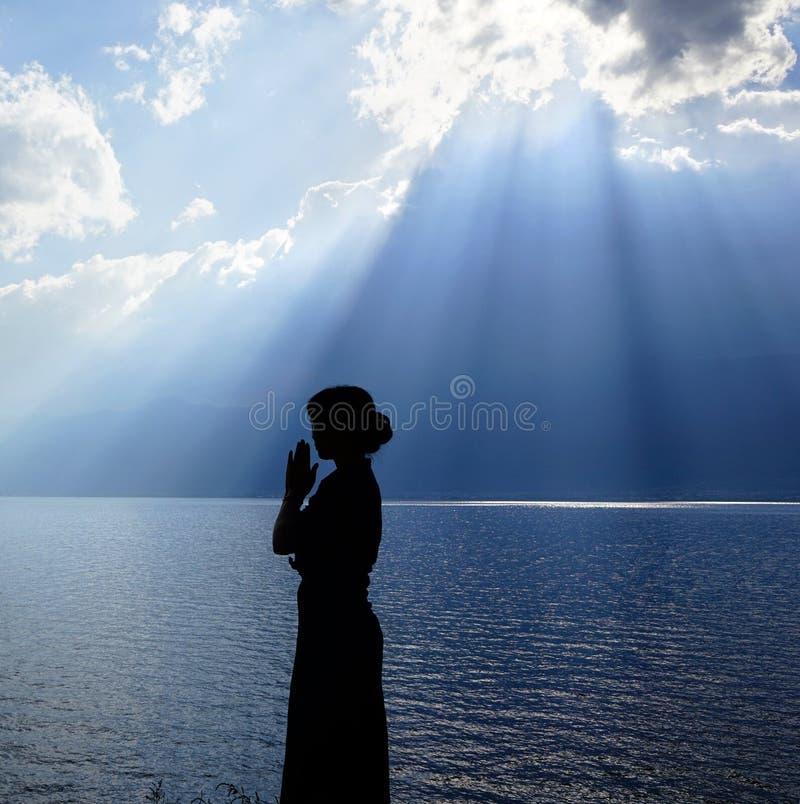 Flicka som ber till guden fotografering för bildbyråer