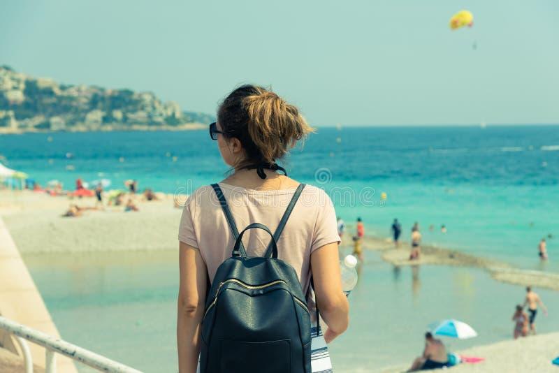 Flicka som beundrar stranden på en solig dag i Nice, Frankrike arkivbilder