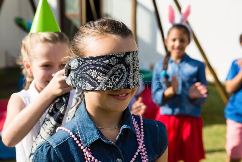 Flicka som binder för ögonen på vännen, medan spela i gård fotografering för bildbyråer