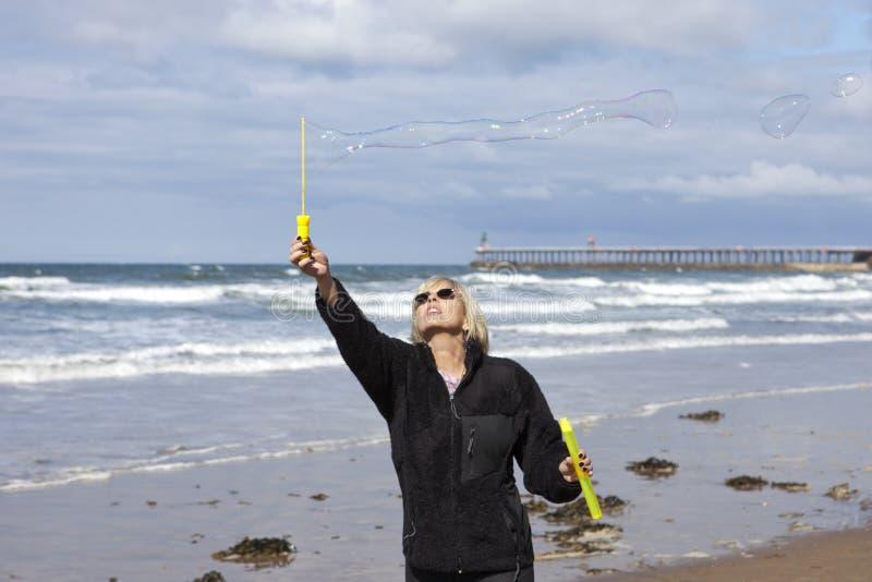 Flicka som blåser såpbubblor på stranden arkivbild