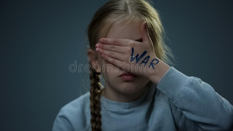 Flicka som d?ljer bak handen med kriginskriften och att hoppas f?r fred och s?kerhet arkivfoto