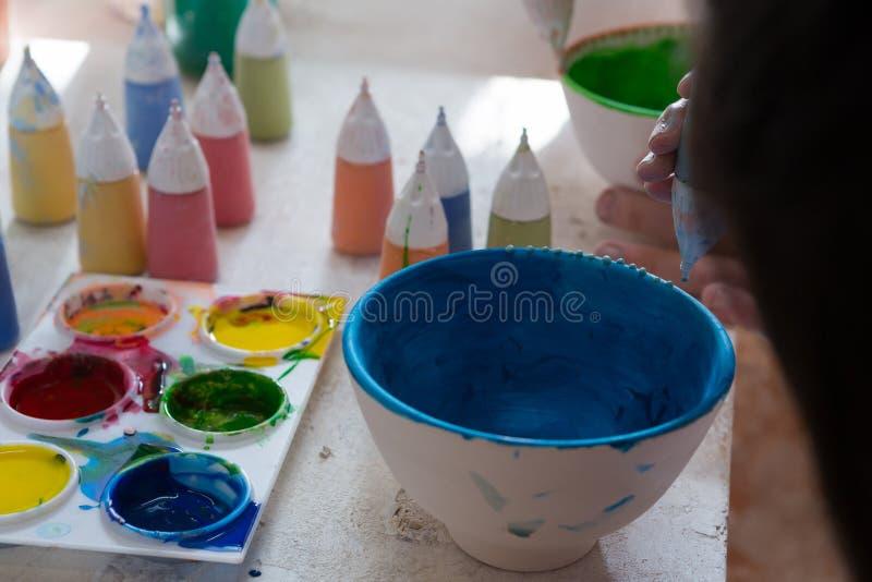 Flicka som dekorerar bunken med målarfärg arkivfoton