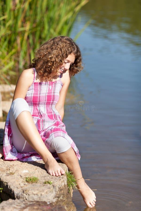 Flicka som doppar foten i vatten arkivbild