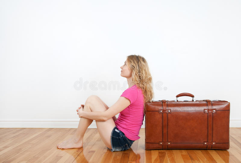 Flicka som drömm och sitter bredvid henne resväska royaltyfria bilder