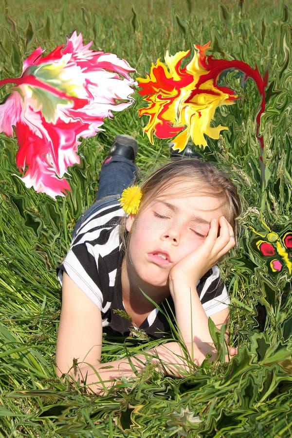 Flicka som drömmer i en blommaträdgård royaltyfri fotografi