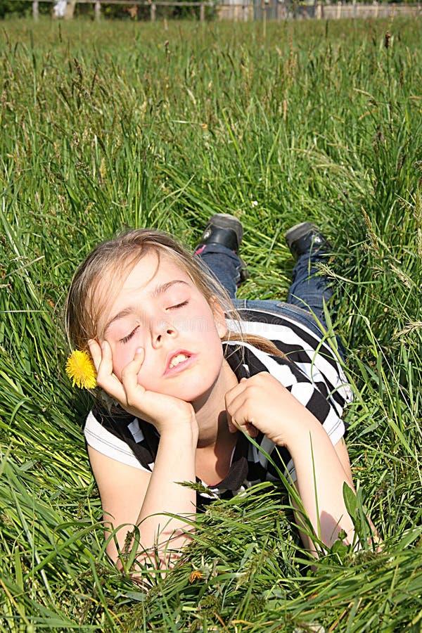Flicka som drömmer på en äng royaltyfri bild