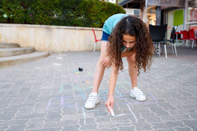 Flicka som drar hoppa hage med krita p? lekplats royaltyfri fotografi