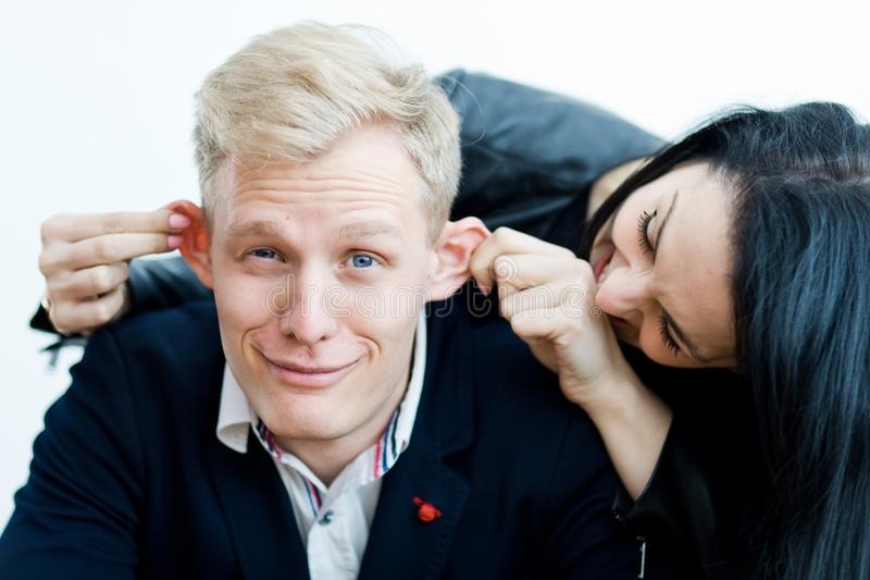 Flicka som drar pojkväns öron för att göra en gyckel royaltyfri bild
