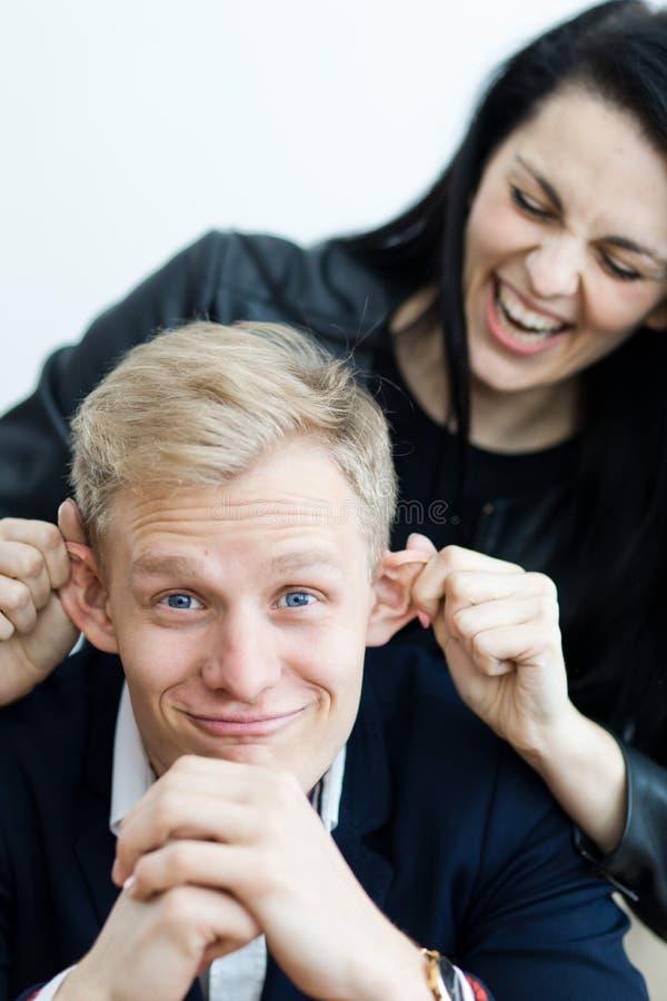 Flicka som drar pojkväns öron för att göra en gyckel arkivbild