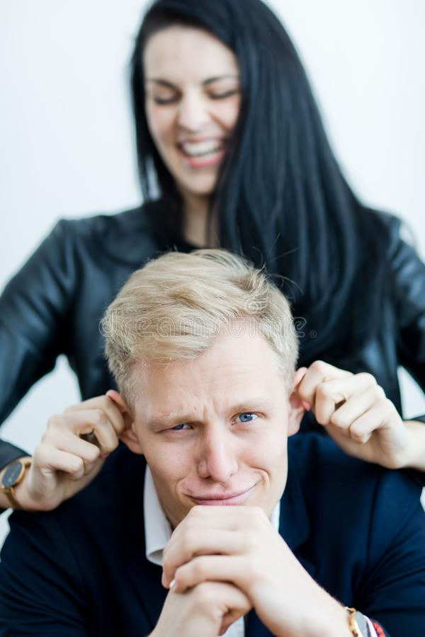 Flicka som drar pojkväns öron för att göra ett roligt - le framsidagrimasen royaltyfria foton