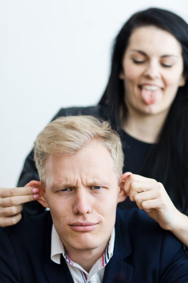 Flicka som drar pojkväns öron för att göra ett roligt - riktig förälskelse fotografering för bildbyråer