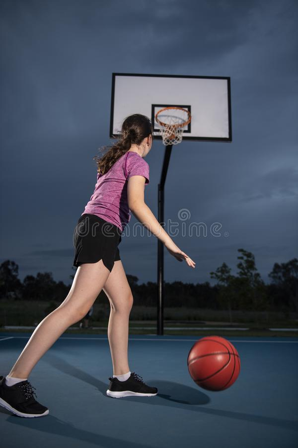 Flicka som dreglar en basket på en utomhus- domstol royaltyfri fotografi